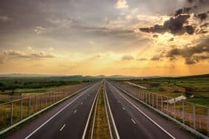 Highway traffic in sunset, travel concept background